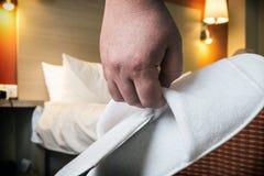 Τα χέρια κρατούν τις άσπρες παντόφλες στο δωμάτιο ξενοδοχείου Στοκ Εικόνα