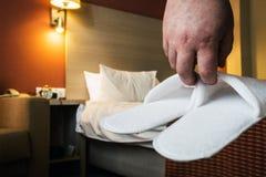 Τα χέρια κρατούν τις άσπρες παντόφλες στο δωμάτιο ξενοδοχείου Στοκ Εικόνες