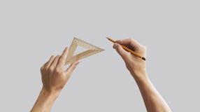 Τα χέρια κρατούν το μολύβι με τον τριγωνικό ξύλινο κυβερνήτη Απομονωμένος gre Στοκ φωτογραφία με δικαίωμα ελεύθερης χρήσης