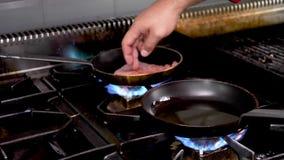 Τα χέρια μαγείρων που τοποθετούν ένα κομμάτι το κρέας απόθεμα βίντεο