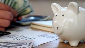 Τα χέρια μετρούν τα χρήματα δολάρια τραπεζών piggy Αποταμίευση ή εγχώρια χρηματοδότηση απόθεμα βίντεο