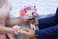 Τα χέρια με τα λουλούδια δέσμευσης, νεόνυμφος βάζουν σε μια δέσμευση ανθίζουν στη νύφη, να ντύσει επάνω μια δέσμευση ανθίζει, νεό στοκ φωτογραφία