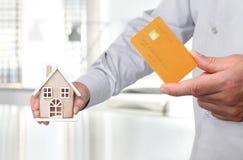 Τα χέρια με το σπίτι και την πιστωτική κάρτα, αγοράζουν το σπίτι Στοκ εικόνα με δικαίωμα ελεύθερης χρήσης