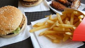 Τα χέρια μιας γυναίκας παίρνουν τις τηγανιτές πατάτες Burgers, φτερά κοτόπουλου, τηγανιτές πατάτες στο δίσκο σε ένα εστιατόριο γρ απόθεμα βίντεο