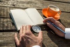 Τα χέρια μιας εκμετάλλευσης ατόμων περιτρηγυρίζουν έτοιμο να γράψουν στο ανοικτό σημειωματάριο Στοκ Εικόνες