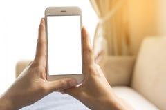 Τα χέρια μιας εργαζόμενης γυναίκας που κρατά ένα έξυπνο τηλέφωνο από την που βρίσκεται στον καναπέ στοκ φωτογραφία με δικαίωμα ελεύθερης χρήσης