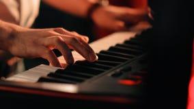 Τα χέρια μιας κινηματογράφησης σε πρώτο πλάνο μουσικών που παίζει το συνθέτη σε μια συναυλία βράχου απόθεμα βίντεο