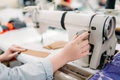 Τα χέρια μοδιστρών ράβουν τα υφάσματα σε μια ράβοντας μηχανή Στοκ φωτογραφία με δικαίωμα ελεύθερης χρήσης