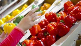 Τα χέρια παίρνουν λίγα ζωηρόχρωμο πιπέρι ένα προς ένα στην αγορά και τη λαβή Κλείστε επάνω την έννοια της επιλογής, αγοράστε τα π φιλμ μικρού μήκους