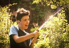 Τα χέρια παιδιών κρατούν τη μάνικα με το νερό στο θερινό ηλιόλουστο πράσινο κήπο Στοκ φωτογραφία με δικαίωμα ελεύθερης χρήσης