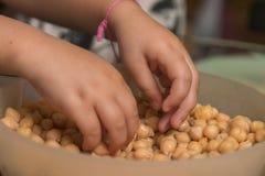 Τα χέρια παιδιών παίρνουν τις φακές στο κύπελλο στοκ φωτογραφία