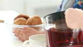 Τα χέρια παιδιών χύνουν το τσάι φρούτων μπροστά από τα χέρια του κοριτσιού που κρατά τα σπιτικά μπισκότα φιλμ μικρού μήκους