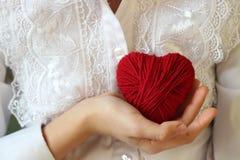 Τα χέρια παιδιών ` s κρατούν μια καρδιά του κόκκινου νήματος για το πλέξιμο Στοκ φωτογραφίες με δικαίωμα ελεύθερης χρήσης