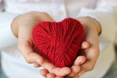 Τα χέρια παιδιών ` s κρατούν μια καρδιά του κόκκινου νήματος για το πλέξιμο Στοκ φωτογραφία με δικαίωμα ελεύθερης χρήσης