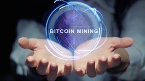 Τα χέρια παρουσιάζουν γύρω από τη μεταλλεία Bitcoin ολογραμμάτων φιλμ μικρού μήκους