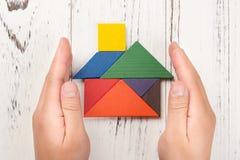 Τα χέρια περιβάλλουν ένα ξύλινο σπίτι που γίνεται από την έννοια εγχώριας ασφάλειας τανγκράμ και αντιπροσώπευση της εγχώριας ιδιο στοκ εικόνα
