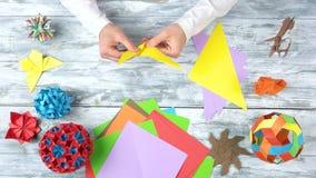 Τα χέρια που κάνουν τον αριθμό origami, κλείνουν επάνω φιλμ μικρού μήκους