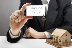 Τα χέρια που κρατούν τη επαγγελματική κάρτα με το κείμενο αγοράζουν ή νοικιάζουν και κλειδιά κτήμα έννοιας πραγματικό Στοκ εικόνες με δικαίωμα ελεύθερης χρήσης