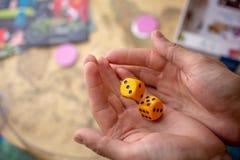 Τα χέρια ρίχνουν κίτρινο χωρίζουν σε τετράγωνα στον τομέα παιχνιδιών Τύχη και ενθουσιασμός Έννοια των επιτραπέζιων παιχνιδιών Στι στοκ εικόνα