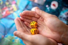 Τα χέρια ρίχνουν κίτρινο χωρίζουν σε τετράγωνα στον τομέα παιχνιδιών Τύχη και ενθουσιασμός Έννοια των επιτραπέζιων παιχνιδιών Στι στοκ εικόνες
