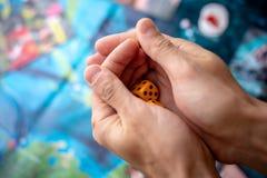 Τα χέρια ρίχνουν κίτρινο χωρίζουν σε τετράγωνα στον τομέα παιχνιδιών Τύχη και ενθουσιασμός Έννοια των επιτραπέζιων παιχνιδιών Στι στοκ φωτογραφία με δικαίωμα ελεύθερης χρήσης