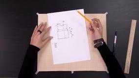 Τα χέρια σχεδιαστών που κάνουν ένα σχέδιο στο ύφασμα πριν από ράβουν τα μοντέρνα ενδύματα απόθεμα βίντεο