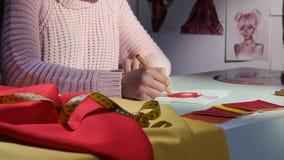 Τα χέρια σχεδιαστών ` s σύρουν ένα σκίτσο ενός όμορφου κόκκινου φορέματος κλείστε επάνω φιλμ μικρού μήκους