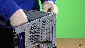 Τα χέρια τεχνικών ξεβιδώνουν και αφαιρούν τη γραφική κάρτα από την περίπτωση υπολογιστών απόθεμα βίντεο