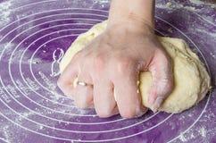 Τα χέρια της γυναίκας ζυμώνουν τη ζύμη σε ένα χαλί σιλικόνης Στοκ φωτογραφία με δικαίωμα ελεύθερης χρήσης