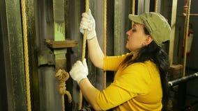 Τα χέρια της γυναίκας ο σκηνικός εργαζόμενος στα γάντια χαμηλώνουν την κουρτίνα θεάτρων και στερεώνουν το καλώδιο φιλμ μικρού μήκους
