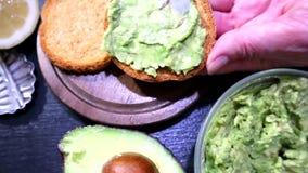 Τα χέρια της γυναίκας που προετοιμάζει το υγιές σάντουιτς αβοκάντο στη σκοτεινή σίκαλη ψήνουν το ψωμί που γίνεται με τη φρέσκια κ απόθεμα βίντεο