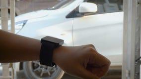 Τα χέρια της γυναίκας που χρησιμοποιεί το έξυπνο ρολόι στην ανοικτή και στενή κλειδαριά και ξεκλειδώνουν την πόρτα της μακρινής έ απόθεμα βίντεο