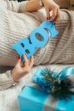 Τα χέρια της εγκύου γυναίκας κρατούν το μπλε ξύλινο αγόρι ` σημαδιών `` πίσω από το μπλε χριστουγεννιάτικο δώρο επάνω Στοκ Φωτογραφία