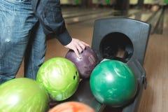Τα χέρια της επιλεγμένης άτομο σφαίρας για το μπόουλινγκ Σφαίρες χρώματος για το μπόουλινγκ στοκ φωτογραφία με δικαίωμα ελεύθερης χρήσης