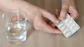 Τα χέρια της ηλικιωμένης γυναίκας παίρνουν την ιατρική απόθεμα βίντεο