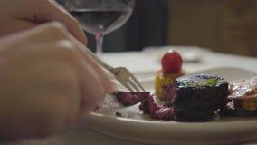 Τα χέρια της νέας γυναίκας που κόβει το νόστιμο φρέσκο κρέας που βρίσκεται στο πιάτο με το φυτικά χρησιμοποιώντας δίκρανο και το  φιλμ μικρού μήκους