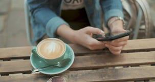 Τα χέρια της νέας γυναίκας χρησιμοποιούν το smartphone κατά τη διάρκεια του διαλείμματος στον καφέ Κλείστε επάνω το μήκος σε πόδη απόθεμα βίντεο
