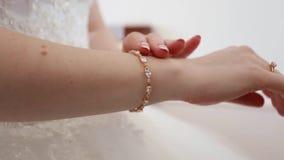 Τα χέρια της νύφης ντύνουν το συμπαθητικό βραχιόλι απόθεμα βίντεο