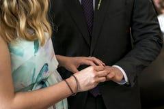 Τα χέρια της νύφης τελετής γάμου γαμήλιων ζευγών βάζουν το δαχτυλίδι στο δάχτυλο του καλού νεόνυμφού της Στοκ φωτογραφία με δικαίωμα ελεύθερης χρήσης