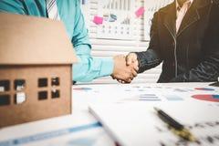 Τα χέρια τινάγματος τραπεζιτών με τον πελάτη για εγκρίνουν το μίσθωμα ένα σπίτι Στοκ Φωτογραφίες