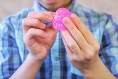 Τα χέρια του αγοριού κρατούν ρόδινο slime Παιχνίδια αγοριών με slime στοκ εικόνες με δικαίωμα ελεύθερης χρήσης