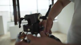 Τα χέρια του αρσενικού θέτουν τα διαφορετικά πράγματα στη μαύρη πλαστική συσκευή στο δωμάτιο φιλμ μικρού μήκους