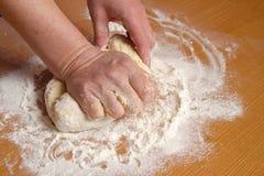 Τα χέρια του αρτοποιού ζυμώνουν τη ζύμη σε ένα αλεύρι στοκ εικόνα με δικαίωμα ελεύθερης χρήσης