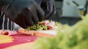 Τα χέρια του αρχιμάγειρα κινηματογραφήσεων σε πρώτο πλάνο μαγειρεύουν το σάντουιτς με το μαρούλι, το ζαμπόν και το τυρί φιλμ μικρού μήκους