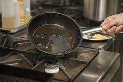 Τα χέρια του αρχιμάγειρα που θερμαίνει το τηγάνι στοκ εικόνες