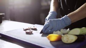 Τα χέρια του αρχιμάγειρα που κόβει το φρέσκο ακατέργαστο κρέας σε μια κουζίνα επιβιβάζονται στην εμπορική κουζίνα φιλμ μικρού μήκους