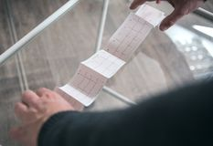 Τα χέρια του ασθενή κρατούν ένα ιατρικό καρδιογράφημα τυπωμένο σε χαρτί στοκ εικόνες με δικαίωμα ελεύθερης χρήσης
