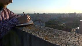 Τα χέρια του ατόμου γράφουν τις σημειώσεις στο ηλιοβασίλεμα στην κορυφή της στέγης φιλμ μικρού μήκους