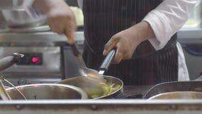 Τα χέρια του επαγγελματικού αρχιμάγειρα ανακατώνουν τα μακαρόνια σε ένα τηγάνι Εργασίες μαγείρων σε μια σύγχρονη κουζίνα με τα μέ απόθεμα βίντεο