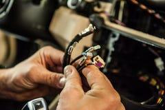 Τα χέρια του εργαζομένου ελέγχουν τα καλώδια στο αυτοκίνητο στοκ εικόνες με δικαίωμα ελεύθερης χρήσης